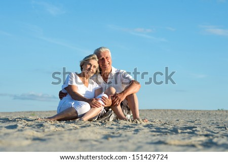 elderly couple went to the beach to enjoy the sea breeze - stock photo