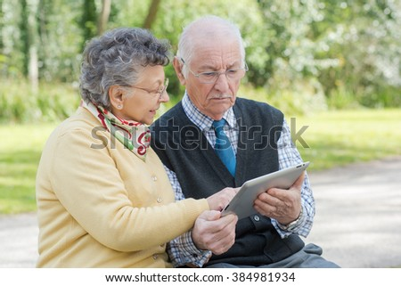 elderly couple with a tablet in the park - stock photo