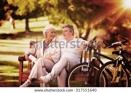 Elderly couple with their bikes against light beam - stock photo