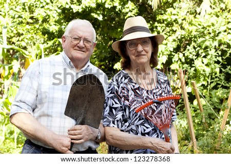 elderly couple working in urban garden - stock photo