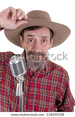 elderly cowboy in checkered red shirt lifting the front of his hat standing behind a retro style microphone isolated on white background