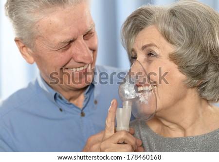 Elderly cute smiling couple making inhalation - stock photo