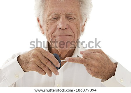 Elderly  diabetic man measuring sugar level in blood using glucometer isolated on white background  - stock photo