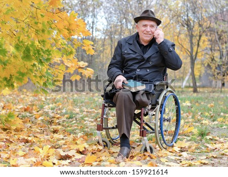 Elderly disabled man sitting in a wheelchair in a chilly colourful park in autumn with a book on his lap chatting on his mobile phone