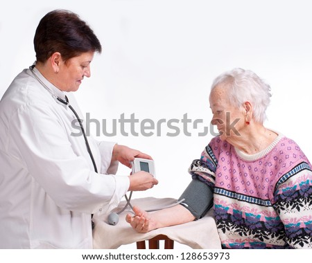 Elderly doctor and patient on a white background. Measuring pressure.