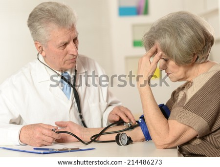 Elderly doctor measuring blood pressure to the senior woman