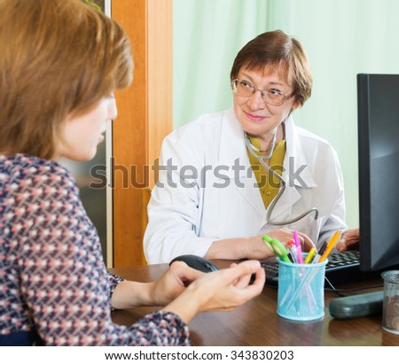 Elderly doctor sitting at computer looking at patient friendly