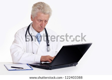 elderly doctor with a laptop on a white
