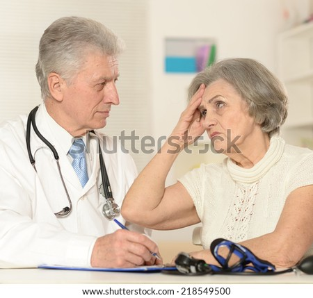 Elderly doctor with a patient on a white background