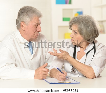 Elderly doctors working at table on a white