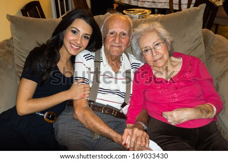 Elderly eighty plus year old grandparents with granddaughter in a home setting. - stock photo