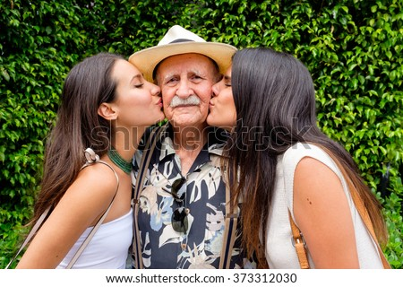 Elderly eighty plus year old man being kissed by his granddaughters in a outdoor setting. - stock photo