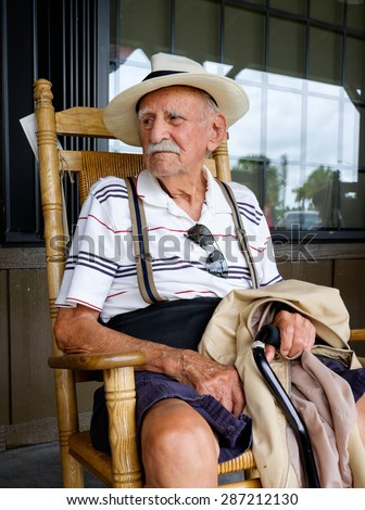 Elderly eighty plus year old man sitting on a rocking chair. - stock photo