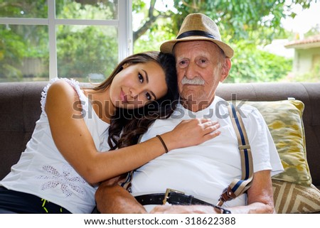 Elderly eighty plus year old man with granddaughter in a home setting. - stock photo