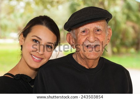 Elderly eighty plus year old man with granddaughter in a outdoor setting. - stock photo
