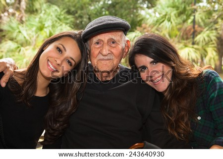 Elderly eighty plus year old man with granddaughters in a outdoor setting. - stock photo