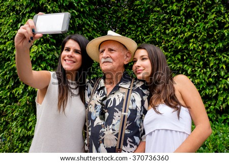 Elderly eighty plus year old man with his granddaughters taking a selfie in a outdoor setting. - stock photo