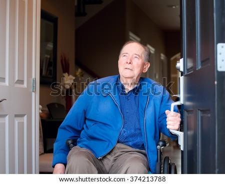 Elderly eighty yr old man in wheelchair at his front door, looking up towards sky - stock photo