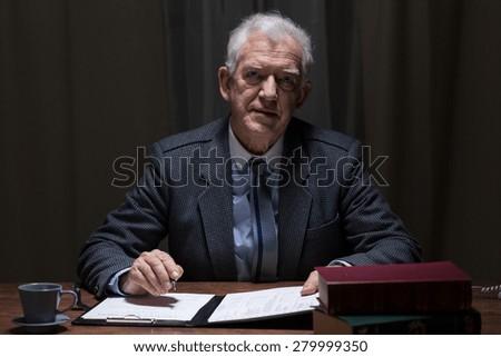 Elderly elegant man sitting alone in his study room - stock photo