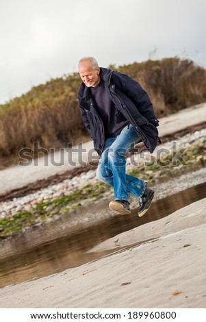Elderly energetic man running along a beach at the edge of a bay on a cold day as he exercises to remain fit and healthy while enjoying nature