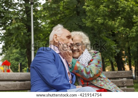 Elderly family couple talking on a bench in a city park - stock photo