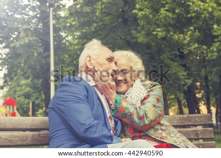 Elderly family couple talking on a bench in a city park. Happy seniors dating - stock photo