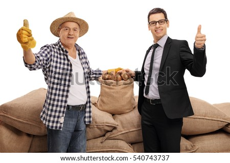 Elderly farmer and a businessman giving thumbs up in front of a pile of burlap sacks filled with potatoes isolated on white background