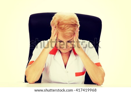 Elderly female doctor or nurse sitting behind the desk with headache - stock photo