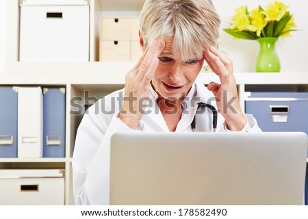 Elderly female doctor with burnout syndrome in her office at the desk