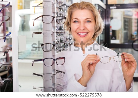 Elderly female optician standing near display with spectacles and smiling