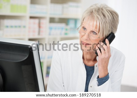 Elderly female pharmacist working in the pharmacy standing at her computer chatting on the phone listening to a patient talking - stock photo