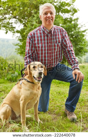 Elderly forester sitting with his dog in nature - stock photo