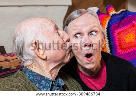 Elderly gentleman kissing elderly woman on cheek in livingroom - stock photo