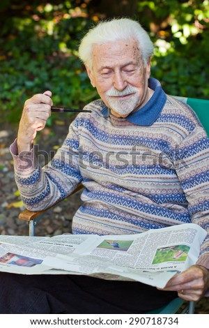 Elderly gentleman reading the newspaper outside in the garden. - stock photo