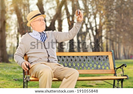 Elderly gentleman taking a selfie wit cell phone, seated on bench in park - stock photo
