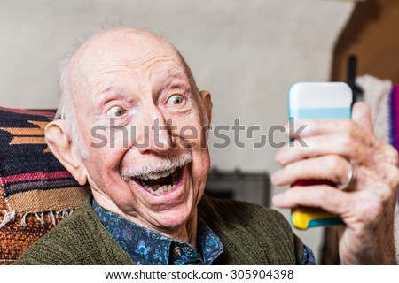 Elderly gentleman taking a selfie with smartphone - stock photo