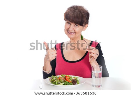 Elderly good looking woman eating green salad. Healthy life style concept - stock photo