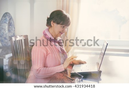 Elderly good looking woman working with laptop. Portrait in domestic interior - stock photo