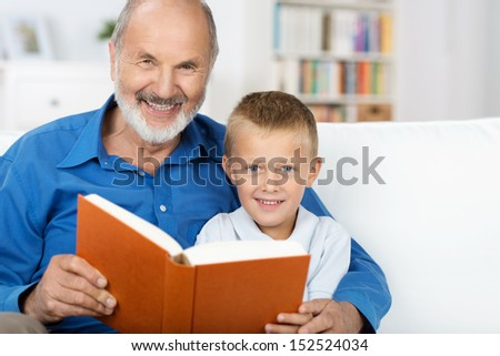 Elderly grandfather and grandson enjoying a book together as they sit reading on a couch in the living room - stock photo