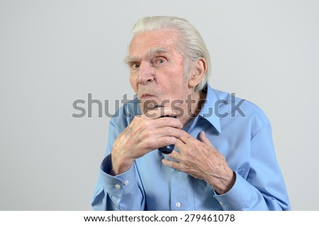 Elderly groomed man wearing a tidy blue shirt while shaving himself with a cordless battery-powered electric razor or shaver, portrait with copy space on gray - stock photo