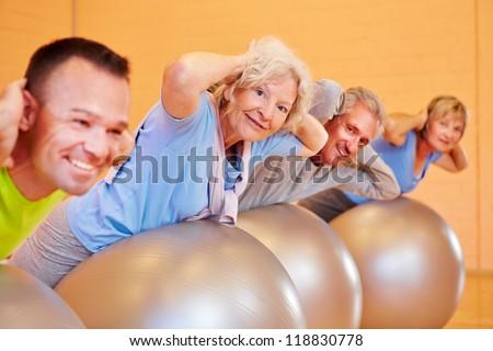 Elderly group doing back exercises in a fitness center - stock photo