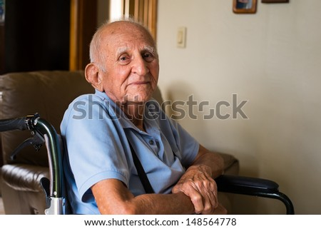 Elderly handicapped eighty plus year old man in a wheel chair in a home setting. - stock photo