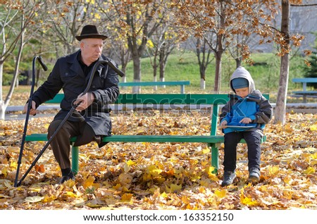 Elderly handicapped man with crutches watching a young boy as the two share a wooden bench in the park as the youngster plays with his tablet computer surfing the internet