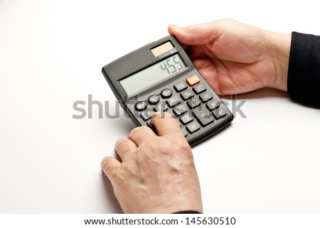 Elderly hands doing calculations on bills, expenses, etc.