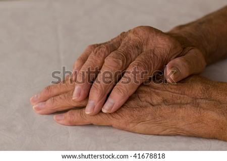 elderly hands folded over white background - stock photo