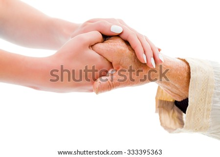 Elderly hands held by a young person - helping concept.