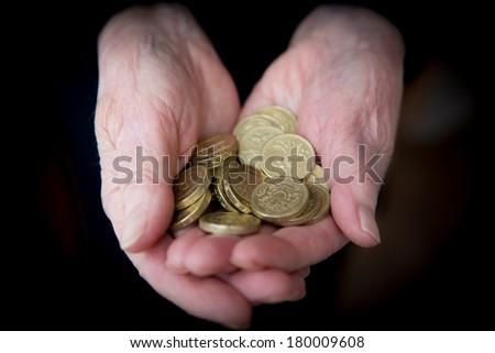 Elderly Hands Holding British Pound Coins - stock photo