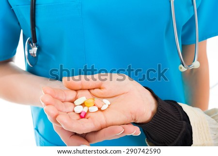 Elderly hands holding large amount of pills given by the doctor in the hospital or residential care. - stock photo