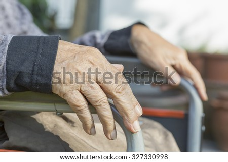 Elderly hands on a wheelchair. - stock photo