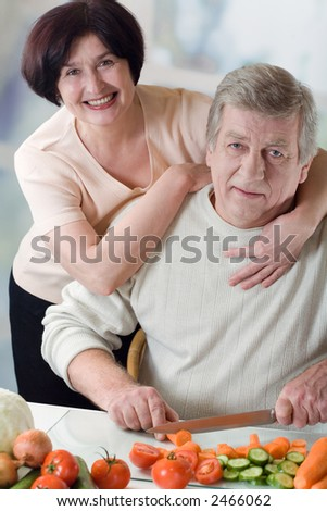 Elderly happy couple cooking at kitchen, embracing - stock photo